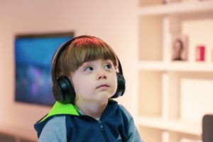 young boy wearing headphones listening to audiobook story