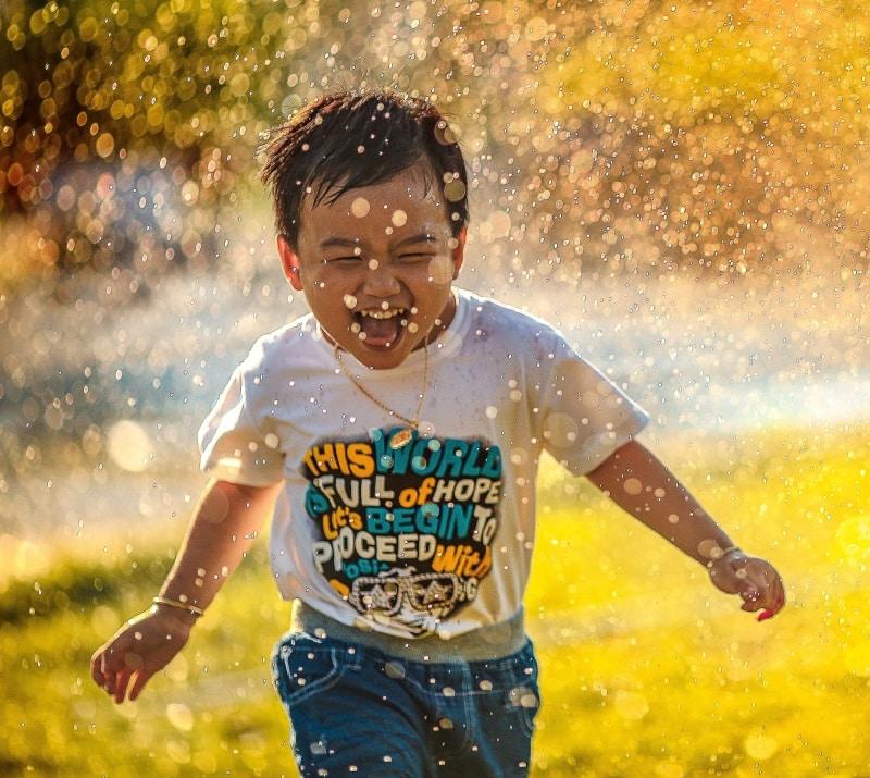 Our Team - boy running through a sprinkler