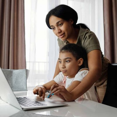Mother helping her daughter using laptop